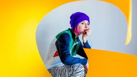 Young girl in 90s style jacket and twist yellow paper. On white background stock photography
