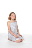 Young girl with sad expression. Young girl on knees with sad expression on her face Stock Photo