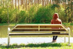 Young girl sad and sit on a wooden bench in the Park, she was disappointed by the sweet love. dreams of the future. Toned Stock Photos