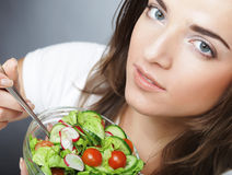 Young  girl with a salad on a white background Stock Photos
