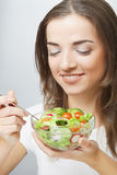Young  girl with a salad on a white background Royalty Free Stock Photography