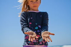 Young girl with sand covered hands Stock Images