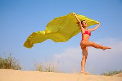 Young girl on sand with yellow shawl in hands Stock Image