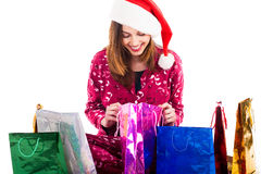 Young girl with santa cap check her shopping bags Stock Photography