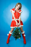Young girl in Santa Claus clothes. Over blue background Royalty Free Stock Images
