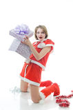 Young girl in Santa Claus clothes with gift box. Surprised young girl in Santa Claus clothes with gift box Royalty Free Stock Photos
