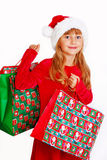 Young girl in santa cloth with gift bags Royalty Free Stock Image