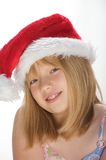 Young girl in a santa hat. Young girl smiling and wearing a santa hat Royalty Free Stock Photos