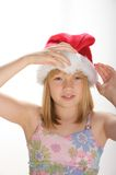 Young girl in a santa hat. Young girl smiling and wearing a santa hat Royalty Free Stock Images