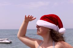 A young girl in a Santa hat on the background of the sea looks into the distance. stock photos