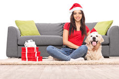 Young girl with Santa hat sitting with her dog Stock Images