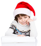 Young girl in Santa hat writes letter to Santa Stock Photos