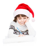 Young girl in Santa hat writes letter to Santa. isolated on white royalty free stock photo