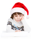 Young girl in Santa hat writes letter to Santa.  on white Royalty Free Stock Photography