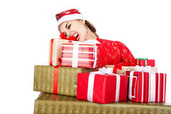 Young girl in Santa hats teeth trying to open a box with a gift Royalty Free Stock Image