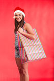 Young girl in Santa`s hat with shopping bag stock photo