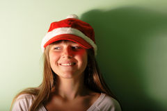 Young girl with Santa's red cap. Stock Photos