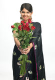 Young girl in sari with red roses Royalty Free Stock Images