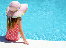 Young girl sat by the pool Stock Image