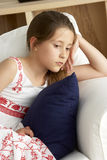 Young Girl Sat on Sofa at Home Royalty Free Stock Photos