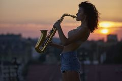 Young girl with a saxophone on the roof stock photo