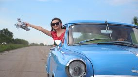 Young girl with scarf in hand leaning out of window of vintage car and enjoying ride. Woman looks out from moving retro