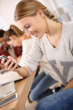 Young girl at school using smartphone Royalty Free Stock Photos