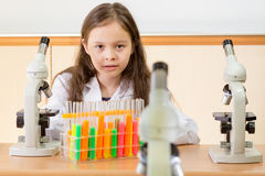 Young girl scientist with microscope and test tubes in science l Stock Images