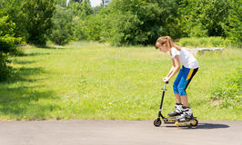 Young girl on a scooter in rollerblades Royalty Free Stock Images