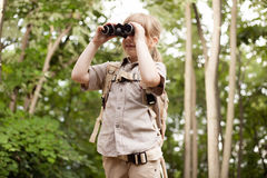 Young girl scout, explores  nature with binoculars on camping tr Stock Photography