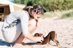 Young girl scratching her lovely dog`s back on summer beach. Young teenage girl scratching her lovely dog`s back sitting at summer beach. Colored vibrant royalty free stock photography