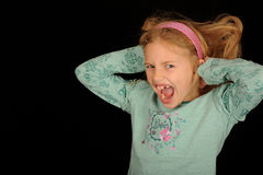 Young girl screaming. A studio portrait of a young girl screaming with hands over her ears.  Black background Royalty Free Stock Photo