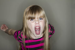 Young girl screaming at the camera. Unhappy young little girl yelling Stock Photo