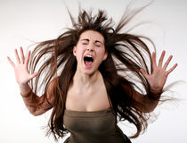 Young girl screaming with flying hair. White background Stock Photos