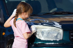 Young Girl Scrubs Car Headlight. Young girl cleans car for pocket money, makes game of it. Handwashing car to save water and earn pocket money royalty free stock photo