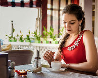 Young girl with scythe in a cafe. Young gGirl with scythe in a red dress with a brooch drinking tea in a cafeirl with scythe in a cafe Stock Photo