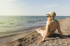 A young girl on the sea coast looking into the distance. Rear view.  stock photography