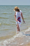 A young girl on the seashore. A young girl, woman in a straw hat walking along the seashore Stock Photos