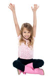 Young girl seated on floor posing with raised arms Royalty Free Stock Images