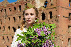 A young girl in a second world war. Epoch head-dress holding a lilac bouquet against the demolished building background Stock Photos