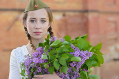 A young girl in a second world war. Epoch head-dress holding a lilac bouquet against the demolished building background Stock Photo