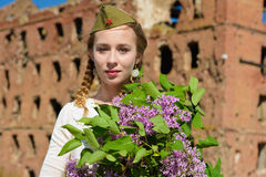 A young girl in a second world war. Epoch head-dress holding a lilac bouquet against the demolished building background Stock Images