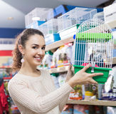 Young girl selecting birdcage for parrot Stock Photo