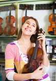 Young girl selecting classical violin Royalty Free Stock Photos