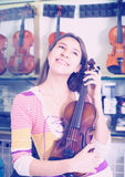 Young girl selecting classical violin. In music instruments studio Royalty Free Stock Images