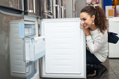 Young girl selecting domestic refrigerator. Cheerful young girl selecting domestic refrigerator in supermarket stock image