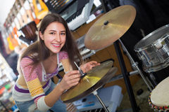Young girl selecting drums and accessories Royalty Free Stock Photography