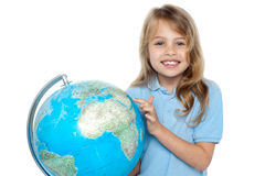 Young girl selecting holiday destination over globe Stock Photography