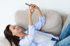 Young girl selfie phone carefree idle leisure. Young beautiful girl taking a selfie using smart phone. carefree idle leisure and social network posting concept royalty free stock photography