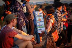 Young girl selling her drawings as postcards to European-looking tourists on one of numerous sunset hills in Bagan, Myanmar stock photography